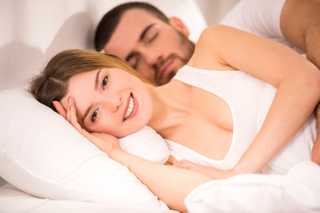 awake: Young happy couple in bed at home
