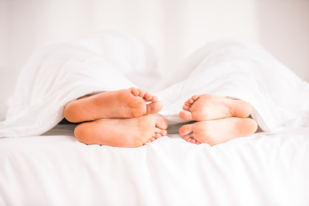 adult foot: The legs from under the blanket. Young happy couple in bed at home Stock Photo