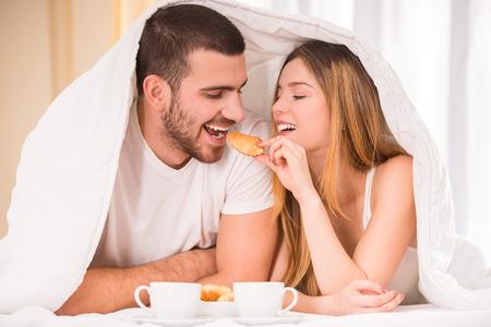 pareja comiendo: Desayunar en la cama. Joven pareja feliz de comer el desayuno en su habitación Foto de archivo