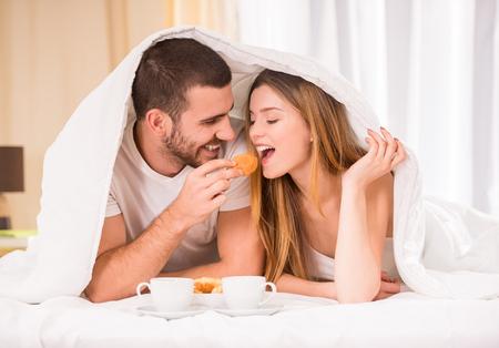 pareja en la cama: Desayunar en la cama. Joven pareja feliz de comer el desayuno en su habitación Foto de archivo