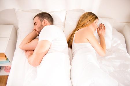 divorcio: Joven pareja durmiendo en la cama de nuevo juntos