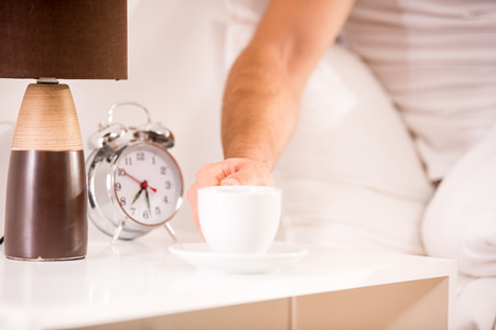 sleeping tablets: A young man drinking coffee, lying in bed at home Stock Photo