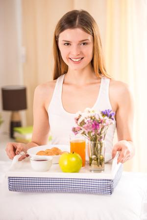 Frühstück im Bett. Junge Frau glücklich essen Frühstück in seinem Schlafzimmer photo