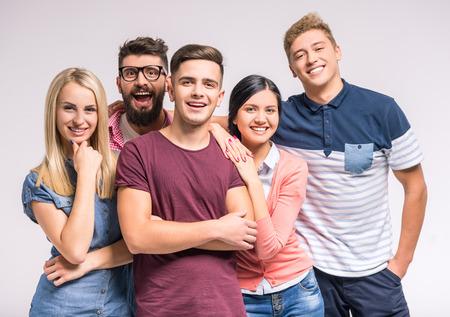 Lustige junge Menschen auf einem grauen Hintergrund