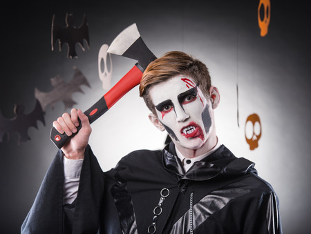 skeleton costume: Happy red hair young man in a skeleton costume holding ax in hand. Studio portrait on black background