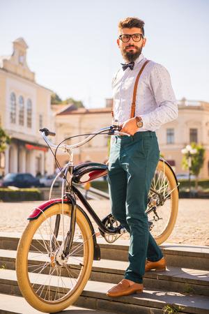 estilo urbano: Bicicleta ciudad. Un hombre joven con barba, a pie de la ciudad con la bici