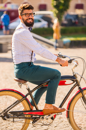 City bike. A young man with a beard, walk the city with bike