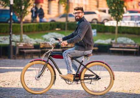 casual men: City bike. A young man with a beard, walk the city with bike