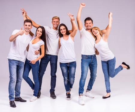 Eine Gruppe von jungen Menschen lächelnd auf einem grauen Hintergrund. Studioaufnahmen