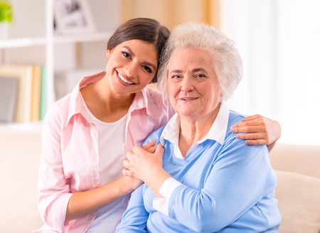 vejez feliz: Cuidado de la mujer mayor en su casa sentado en el sofá