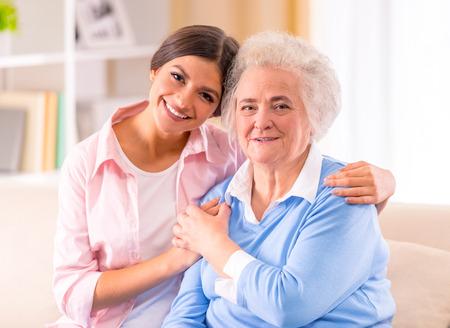 Verzorging van senior vrouw thuis zitten op de bank Stockfoto