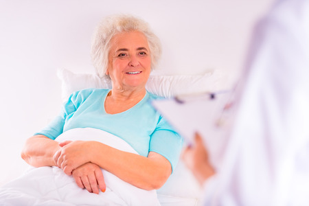 caring for: Caring for a sick senior woman in hospital Stock Photo