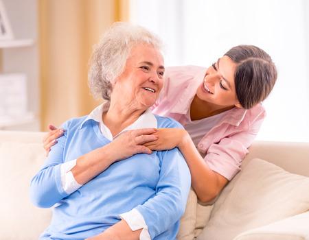 ancianos felices: Cuidado de la mujer mayor en su casa sentado en el sofá