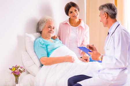 visits: Caring for a sick senior woman in hospital Stock Photo