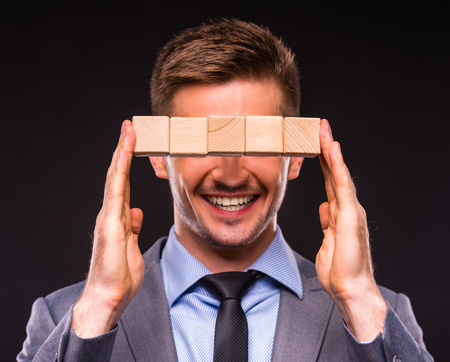 establishes: Creative idea. Young businessman presenting creative idea using wood cubes. Studio shooting isolated on Black background