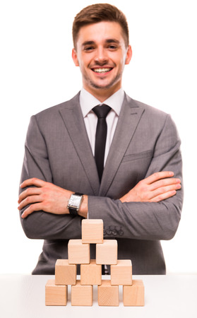 establishes: Creative idea. Young businessman presenting creative idea using wood cubes. Studio shooting isolated on white background