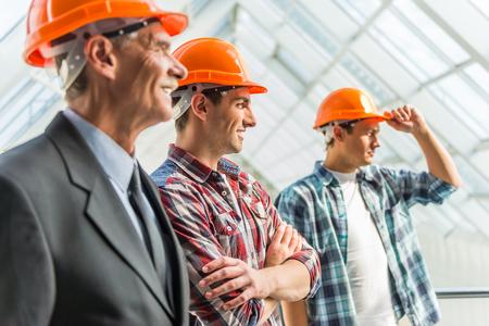 albañil: Retrato de ingenieros masculinos constructor en el casco amarillo en el centro de la oficina