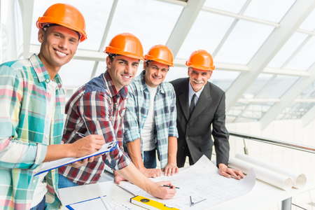 Portrait of male engineers builder in yellow helmet in the office center Фото со стока