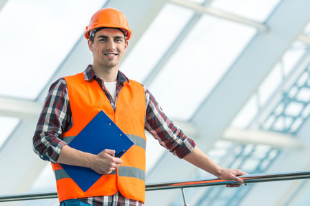 builder: Portrait of a man construction builder in yellow helmet and vest the office center