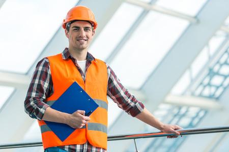 albañil: Retrato de un constructor hombre de la construcción en el casco amarillo y el chaleco del centro de la oficina