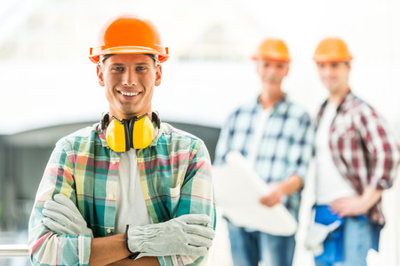 オフィス センターに黄色いヘルメットの男性エンジニア ビルダーの肖像画
