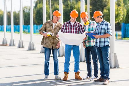 Portrait of male engineers builder in yellow helmet, office center background Banco de Imagens