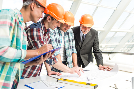 civil engineer: Portrait of male engineers builder in yellow helmet in the office center Stock Photo