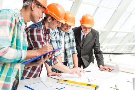 ingeniero civil: Retrato de ingenieros masculinos constructor en el casco amarillo en el centro de la oficina