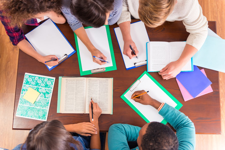 teamwork together: Group young people, students sitting at a table in the classroom Stock Photo