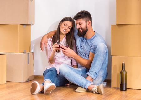 Jong gelukkige paar drinken van wijn, het vieren verhuizen naar nieuw huis