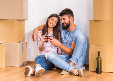 packing: Young happy couple drinking wine, celebrating moving to new home