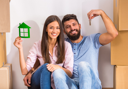 first move: Young happy couple holding keys of new home, moving to a new home concept