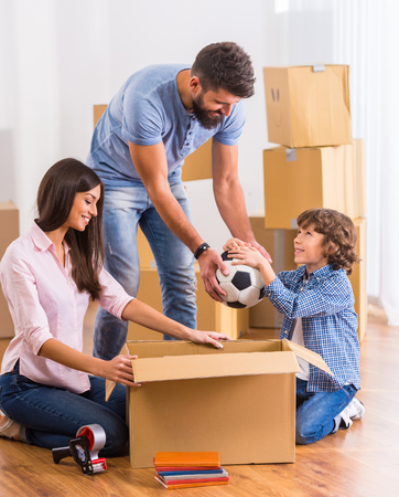 Young happy family moving to a new home, opening boxes