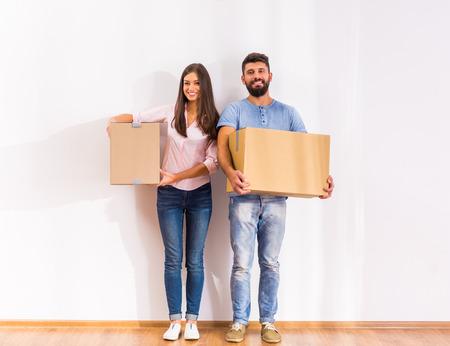 Junge glückliche Paare, Umzug in ein neues Zuhause mit Kartons Standard-Bild - 46977826