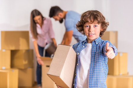 Young happy family moving to a new home with boxes Stockfoto