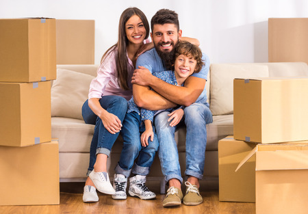 Young happy family moving to a new home with boxes Banque d'images