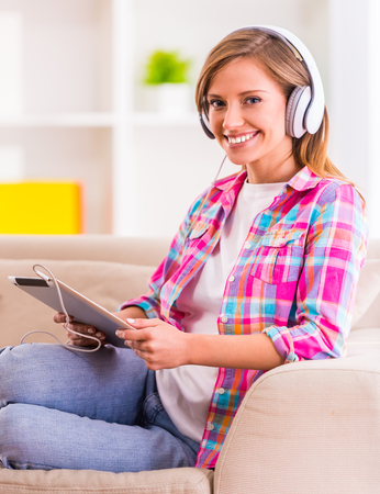 listening: Portrait of a young beautiful woman with headphones sitting on the couch at home and listening to music Stock Photo