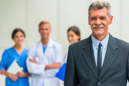 Patron. Senior male businessman shakes hands doctors in hospital