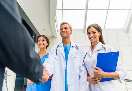 Patron. Senior männlichen Geschäftsmann schüttelt Hände Ärzte im Krankenhaus