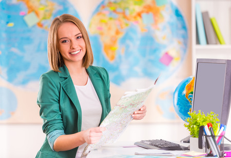 Portrait of a young woman chooses a place to travel using map sitting in office travel agency