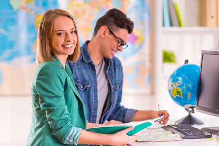 Portrait of a young man and woman chooses a place to travel through area, sitting in office travel agency Stock Photo