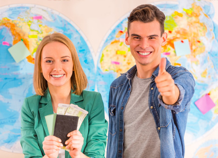passport: Portrait of a young man and woman chooses a place to travel through area, sitting in office travel agency Stock Photo