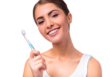 Retrato de una mujer hermosa con las paréntesis en los dientes, limpia los dientes con el cepillo de dientes, aislado en un fondo blanco