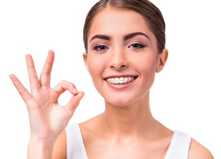 ortodoncia: Retrato de una mujer hermosa con las paréntesis en los dientes, aislados en un fondo blanco