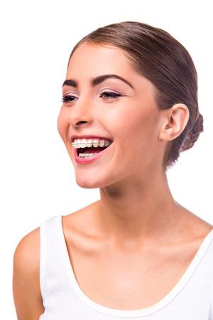 白い背景で隔離の歯にブレースと美しい女性の肖像画 写真素材