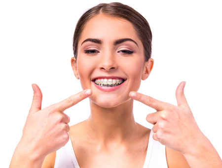 cute braces: Portrait of a beautiful woman with braces on teeth, isolated on a white background