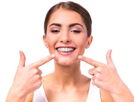 orthodontics: Retrato de una mujer hermosa con las par�ntesis en los dientes, aislados en un fondo blanco