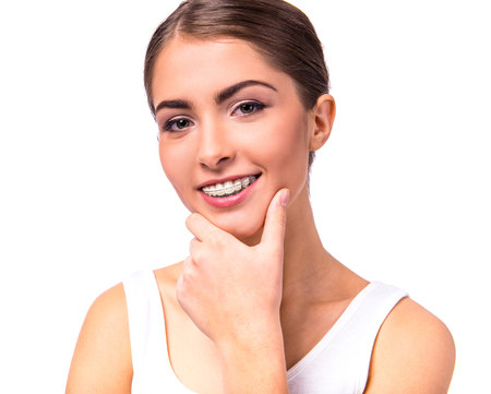 Portret van een mooie vrouw met beugels aan de tanden, die op een witte achtergrond
