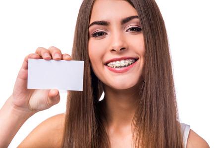 Retrato de una mujer hermosa con las paréntesis en los dientes, aislados en un fondo blanco