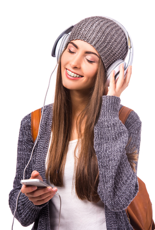 braces: Portrait of a beautiful woman student with braces on the teeth, listening to music, isolated on a white background
